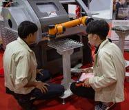 Braço do robô do controle do trabalhador a carregar e a descarregar o workpiece fotografia de stock royalty free