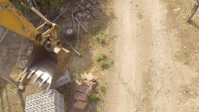 Braço e cubeta da máquina escavadora vistos de cima de filme