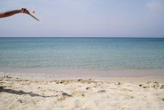 braço, raquete, bola ao jogar na praia com mar azul Fotografia de Stock