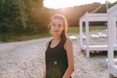 Braços abertos da mulher forte da confiança sob o nascer do sol no beira-mar fotografia de stock royalty free