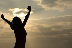 Braços abertos da mulher grata ao nascer do sol imagem de stock