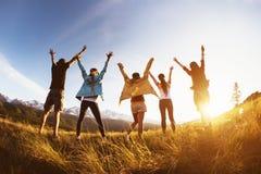Braços aumentados das montanhas dos amigos do grupo por do sol feliz fotografia de stock
