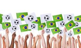 Braços aumentados guardando bandeiras do conceito de Worldcup Brasil imagens de stock royalty free