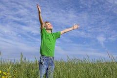 Braços cristãos felizes do menino aumentados na oração foto de stock royalty free