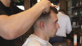 Braços do barbeiro que aparam o cabelo do cliente no salão de beleza Mãos masculinas do cabeleireiro que penteiam e que cortam o  filme
