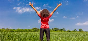 Braços fêmeas do corredor da menina da mulher aumentados no panorama verde do campo foto de stock royalty free