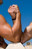 Braços Muscled sob o céu azul Imagens de Stock Royalty Free