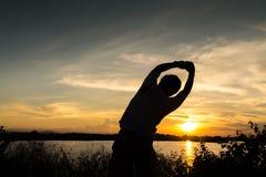 Braços próximos do homem sob o nascer do sol Fotos de Stock Royalty Free