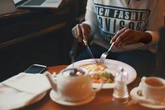 Braços pretos usando a forquilha e a faca para comer a omeleta Fotos de Stock Royalty Free