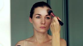 Brać daleko jej makijaż Piękny rozochocony młodej kobiety używać szczotkarski i patrzeć jej odbicie w lustrze zbiory