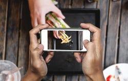 Brać karmową fotografię mądrze telefonem, karmowa fotografia, świetlicowa kanapka z francuzem smaży na drewnianym stole Fotografia Royalty Free