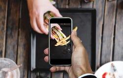 Brać karmową fotografię mądrze telefonem, karmowa fotografia, świetlicowa kanapka z francuzem smaży na drewnianym stole Obrazy Royalty Free