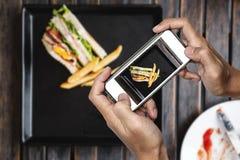 Brać karmową fotografię mądrze telefonem, karmowa fotografia, świetlicowa kanapka z francuzem smaży na drewnianym stole Zdjęcie Stock