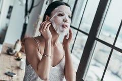 Brać opiekę ona Atrakcyjna młoda kobieta stosuje twarzowego m fotografia royalty free