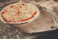 Brać surową pizzę z metal łopatą dla piec Obrazy Stock