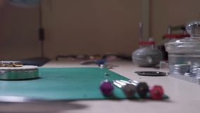 Brać w dół zegarmistrza obiektyw i stawiający na stole zbiory