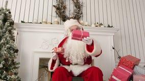 Bra gammalt Santa Claus sammanträde i en stol vid beskriva för spis vad framlägger honom som är förberedd för jul lager videofilmer