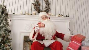 Bra gammalt Santa Claus sammanträde i en stol vid beskriva för spis vad framlägger honom som är förberedd för jul arkivbilder