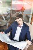 Bra morgon! Affärsman som läser en tidning på kafét som sörjer Royaltyfri Bild