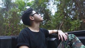 Bra seende asiatisk grabb som baktill sitter av varubilbilen och förnyar sig med ren luft av skogen arkivfilmer