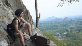 Bra seende asiatisk grabb som sitter på klippan och nöjet med en sikt från överkant stock video