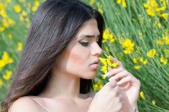 Bra seende dam som luktar den gula blomman arkivbilder