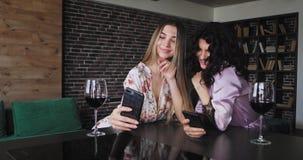 Bra seende damer, i att le för pyjamas som är stort och att göra naturlig nätt framsidastund att ta selfiesna med deras smartphon stock video