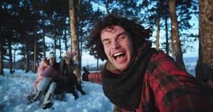 Bra seende grabb med lockigt hår och två hans vänner som tycker om tiden i en vinterdag i mitt av skogen som de tar stock video