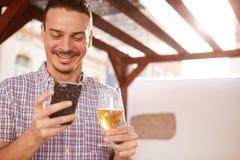 Bra seende grabb som grinar på mobiltelefonen arkivbild