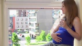 Bra seende gravid kvinnadrinkvatten på fönsterfönsterbräda lager videofilmer