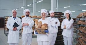 Bra seende huvudsakligt lag i en tekniker för bagare för bageribransch som ser rak till kameran och le som är nätta i ett stort lager videofilmer