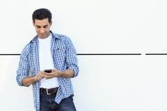 Bra seende man som bär tillfällig kläder som skriver med en smartpho Royaltyfri Foto