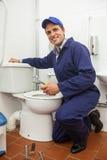 Bra seende rörmokare som reparerar toaletten arkivfoton