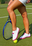 Bra sportar lägger benen på ryggen ställningar med racket på domstolen på den soliga sommardagen Arkivbild