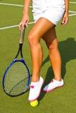 Bra sportar lägger benen på ryggen ställningar med racket på domstolen på den soliga sommardagen Royaltyfri Bild