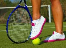 Bra sportar lägger benen på ryggen ställningar med racket på domstolen på den soliga sommardagen Royaltyfri Foto