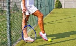 Bra sportar lägger benen på ryggen ställningar med racket på domstolen på den soliga sommardagen Arkivfoto