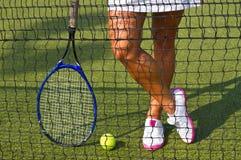 Bra sportar lägger benen på ryggen ställningar med racket på domstolen på den soliga sommardagen Royaltyfria Bilder
