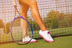 Bra sportar lägger benen på ryggen ställningar med racket på domstolen på den soliga sommardagen Royaltyfri Fotografi