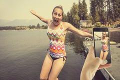 Brać zabaw fotografie na twój smartphone przy jeziorem Fotografia Royalty Free