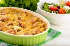 Braadpan met aardappels, worsten, tomaten en kaas stock foto
