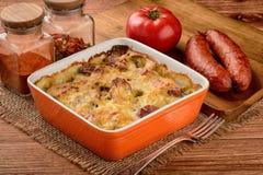 Braadpan met aardappels, worsten, tomaten en kaas stock afbeeldingen
