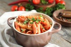 Braadpan van smakelijke pennedeegwaren met tomatensaus op lijst stock afbeelding