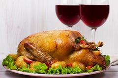 Braadstukeend met aardappel, appelen, salade, thyme en rozemarijn Twee glazen rode wijn Stock Afbeelding
