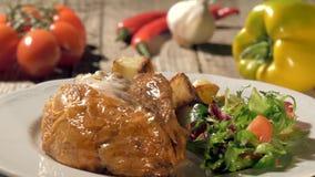 Braadstukkip met aardappelen in de schil en salade stock videobeelden