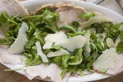 Braadstukruggegraat van varkensvlees met arugula en parmezaanse kaas stock afbeelding