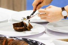 Braadstukrundvlees en plak, de handen die van de chef-kok braadstukrundvlees snijden, die braadstukrundvlees snijden stock afbeeldingen