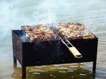 braadstukvlees op vleespennen op open brand Stock Foto
