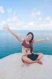 Braccia asiatiche di seduta e di aumento della ragazza in mare Fotografie Stock Libere da Diritti
