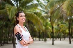 Bracciale d'uso dello smartphone della donna di forma fisica alla spiaggia Fotografia Stock Libera da Diritti
